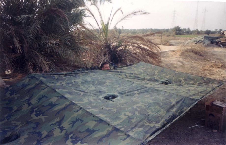My squad leader under his poncho, trying to replicate that cartoon of the guy who is peeking over a wall with his nose hanging over the top. (As Samawah, March 31, 2003)