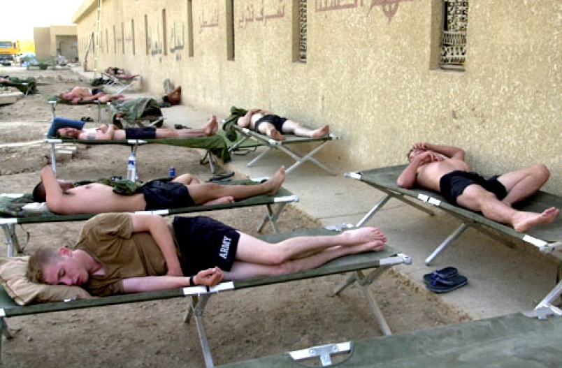 Soldiers sleeping on cots. Stars and Stripes, Oct. 2003